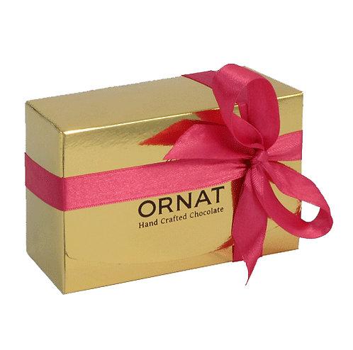 קופסה מלבנית בצבע זהב עטופה כמתנה בסרט ורוד כהה. מכילה 8 פרלינים בטעמים שונים