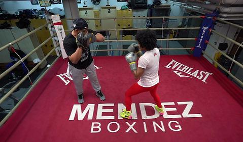 Raquel Harris punching mitts at Mendez Boxing Gym.