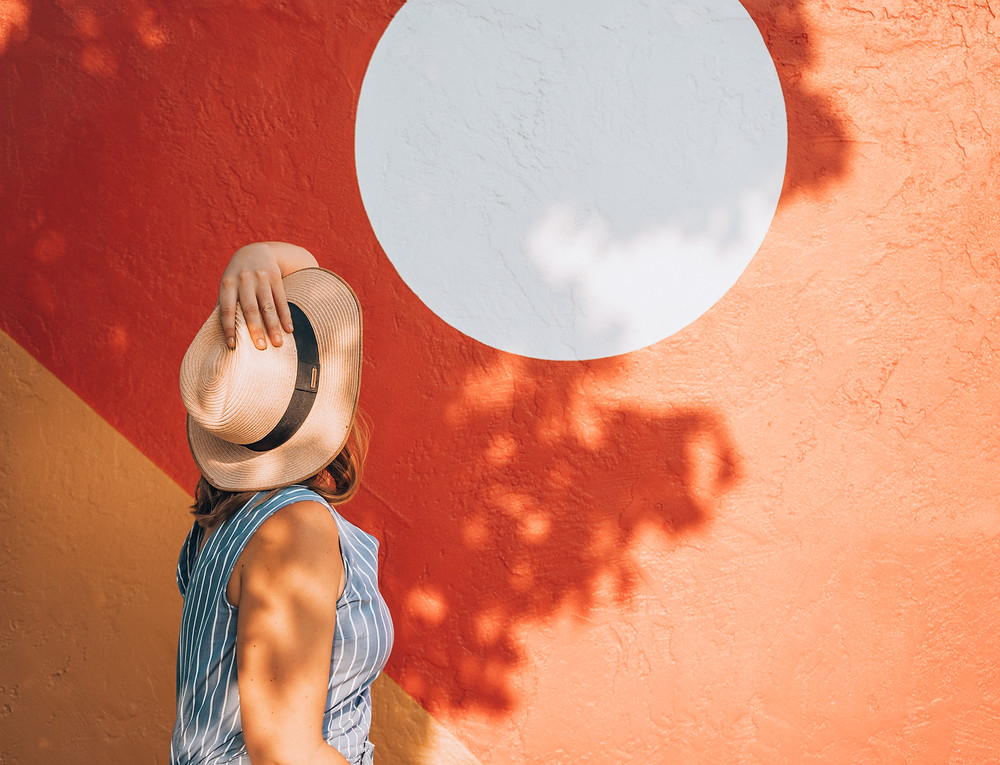 Sasha tilts her head back with her hand on her hat to look at an artistic wall painted orange with a giant white circle in the middle.