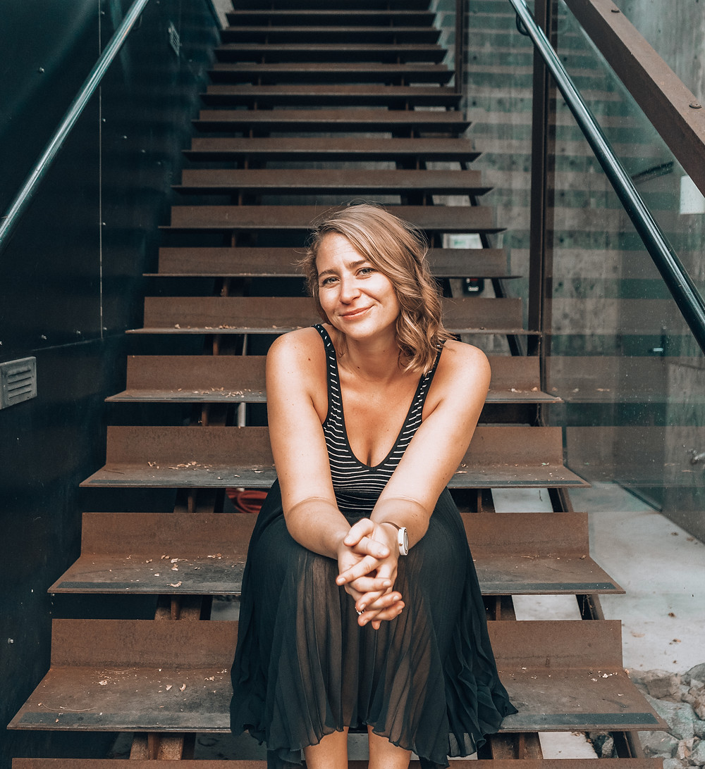 Sasha sits on a modern-looking wooden and glass staircase with her hands in her lap.