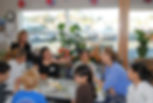 Five people talking at a table in a cooking class
