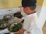 A young boy cooking food on the stove