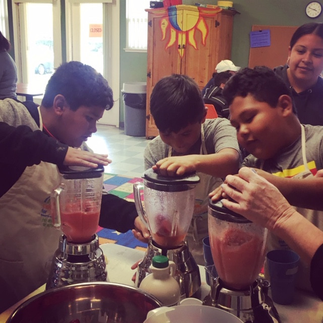 Three young boys in cooking class blending