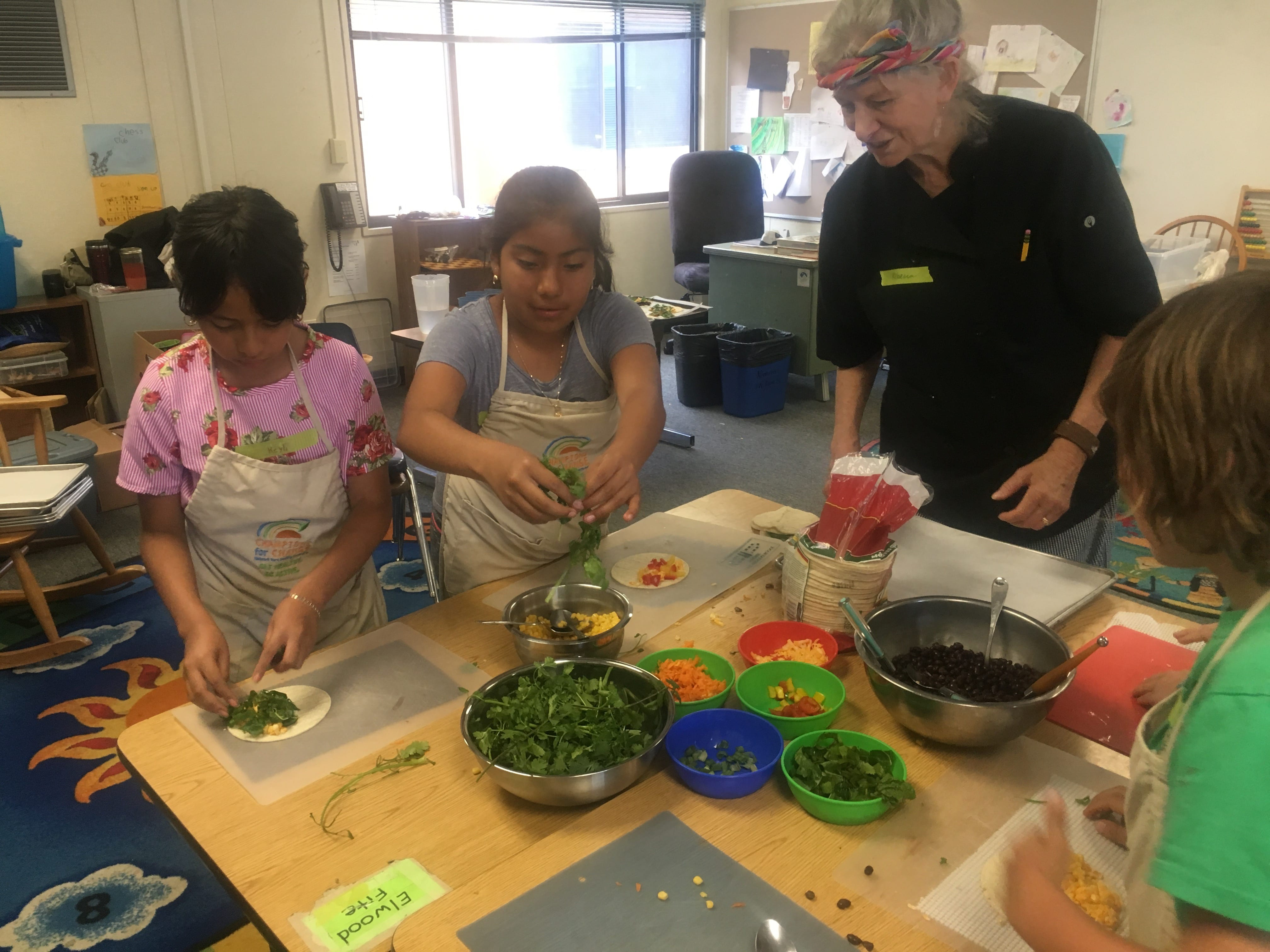 2 students and teacher cooking in class