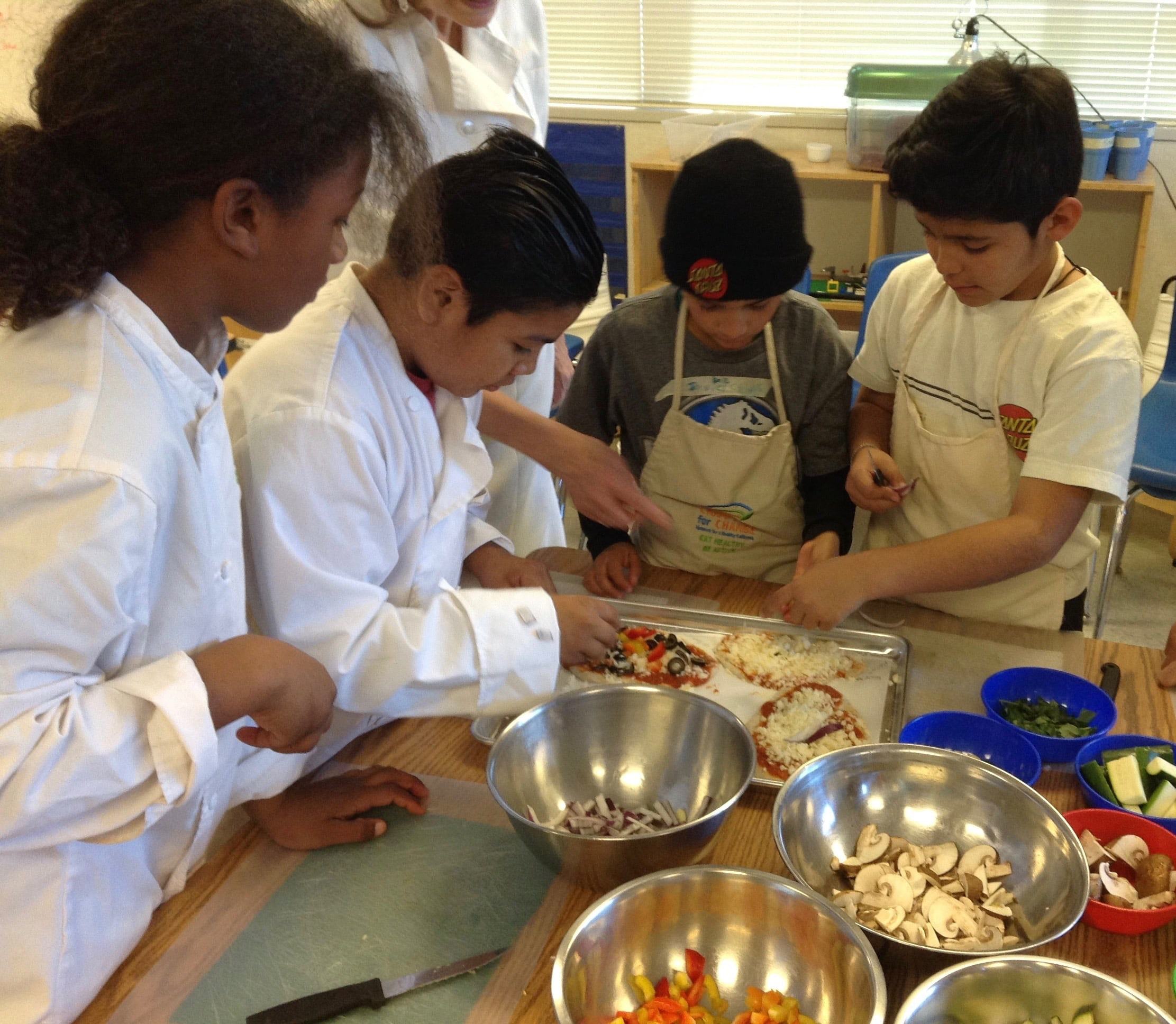4 students in aprons cooking in a nutrition class