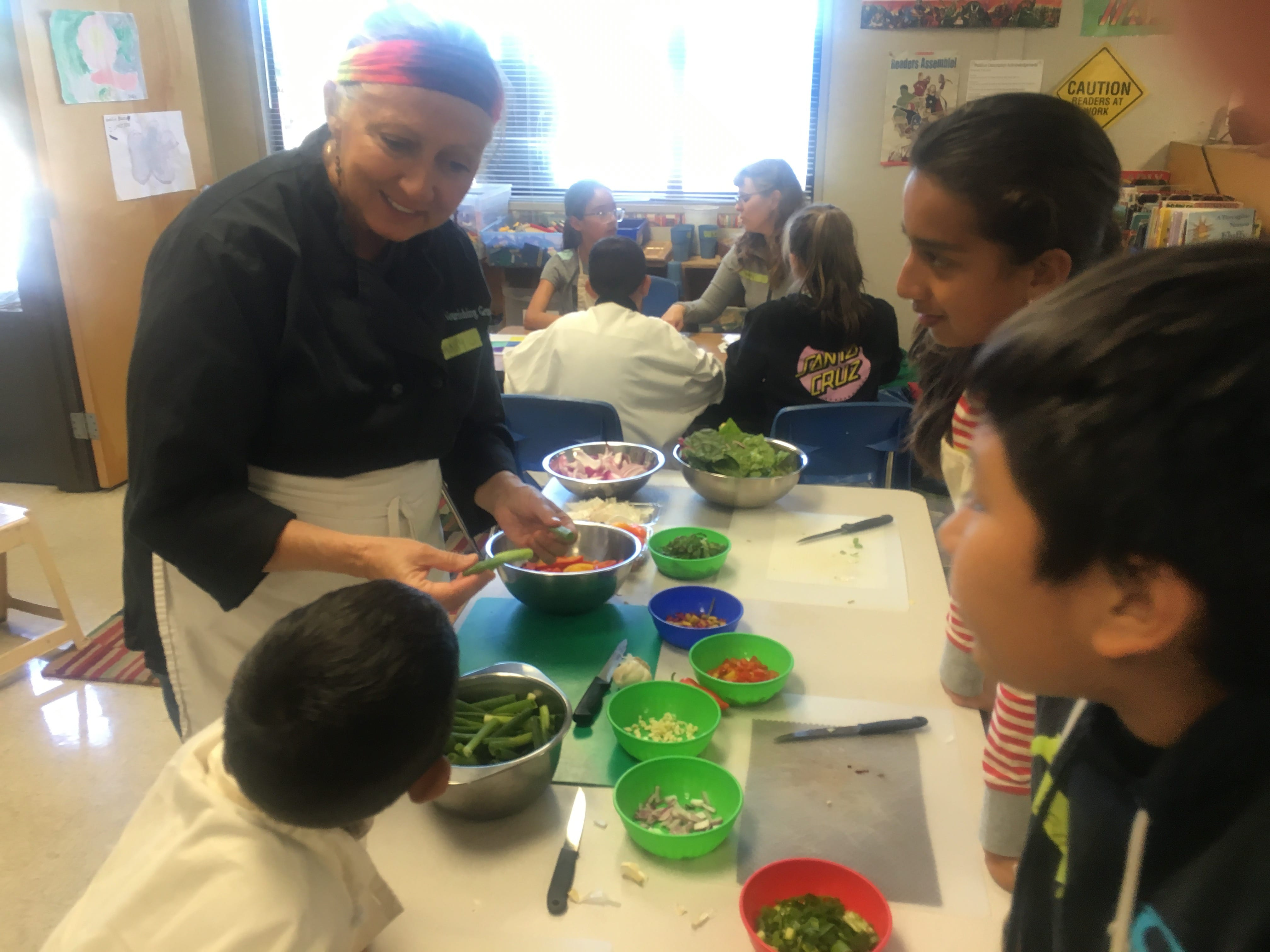 teacher showing cooking skills to 3 students
