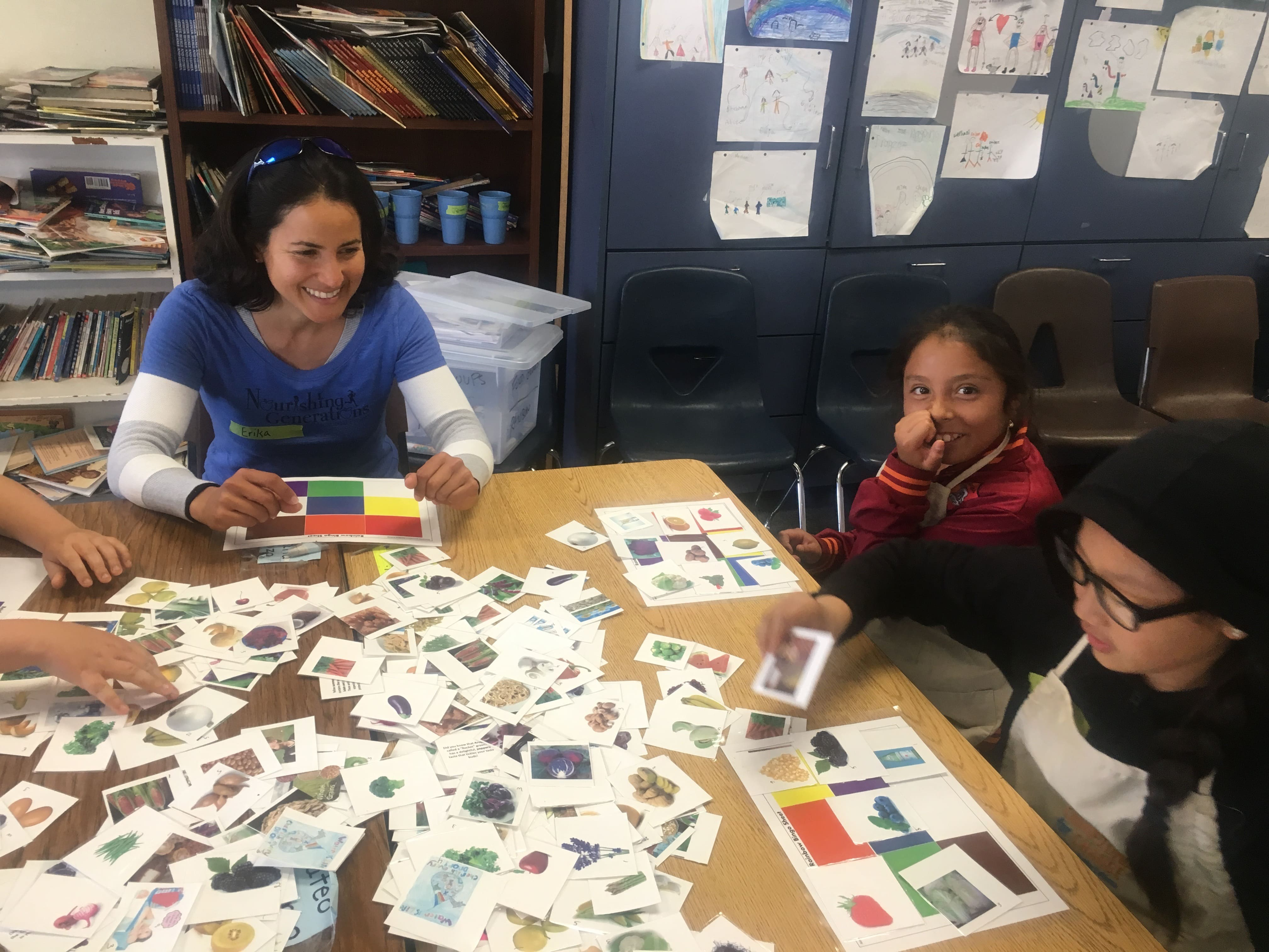 2 students playing a nutrition matching game with a teacher