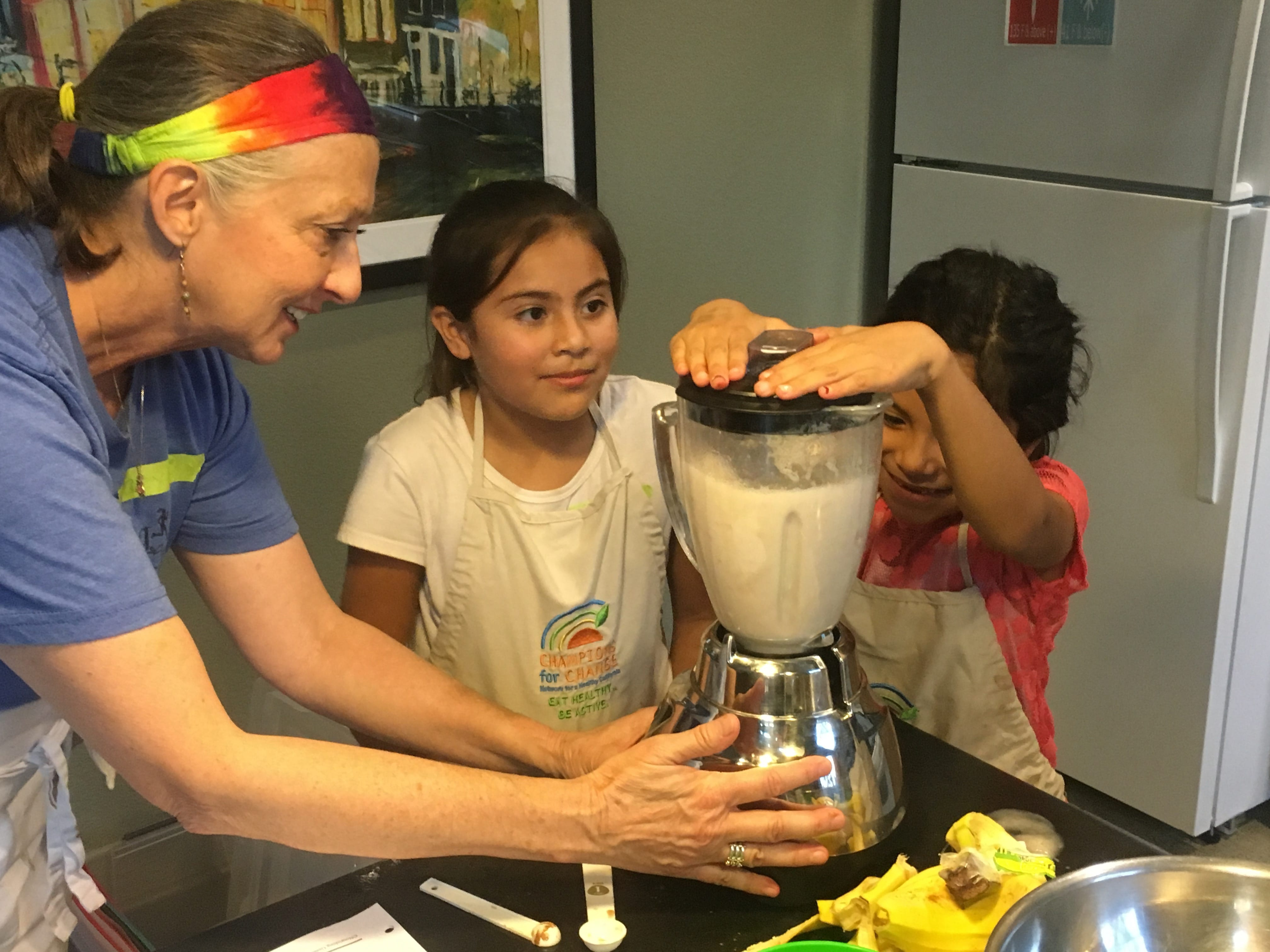 2 students blending with help from a nutrition teacher