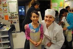 A nonprofit cooking volunteer with a young gir in cooking class