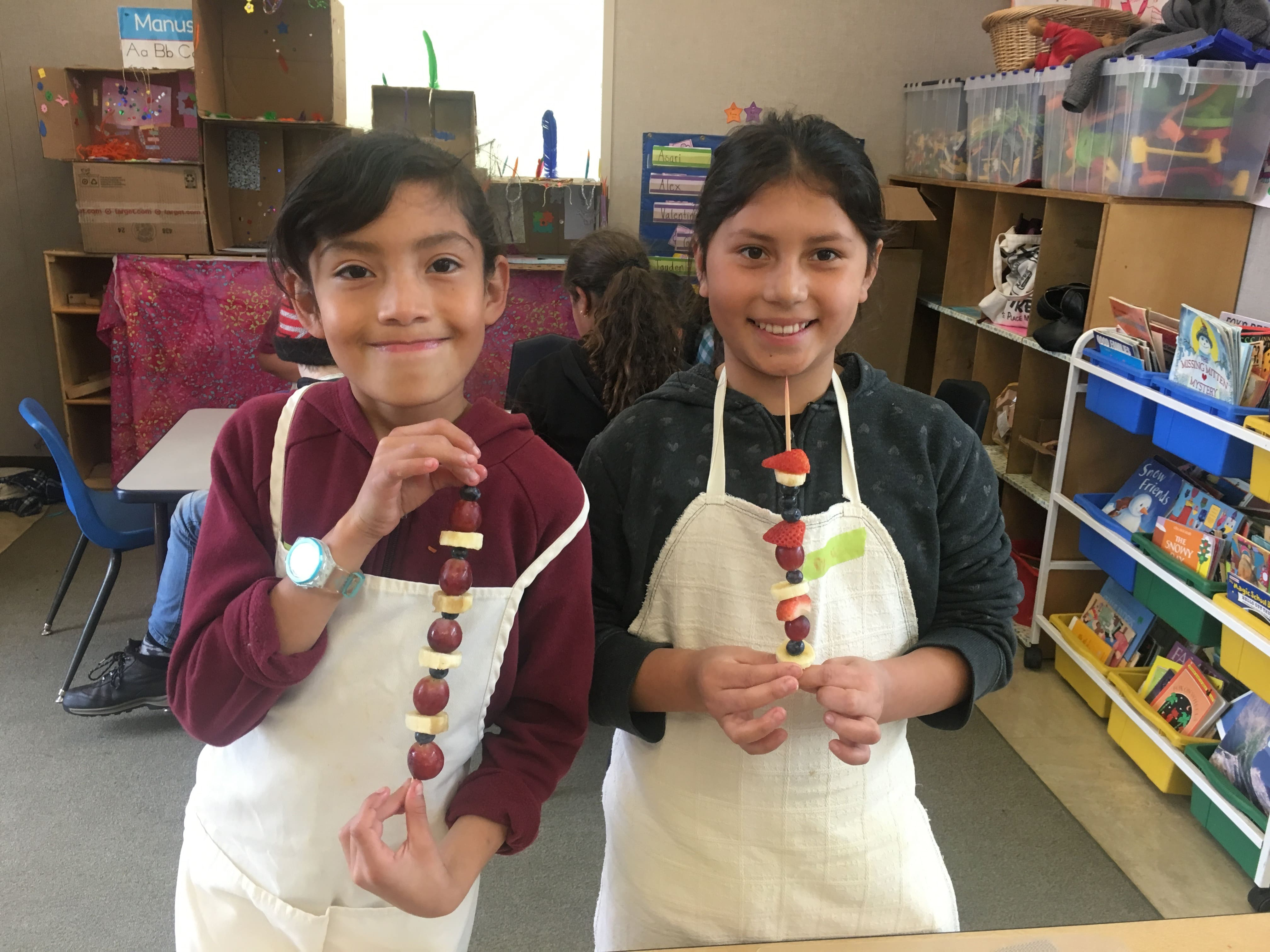 2 students holding fruit kabobs