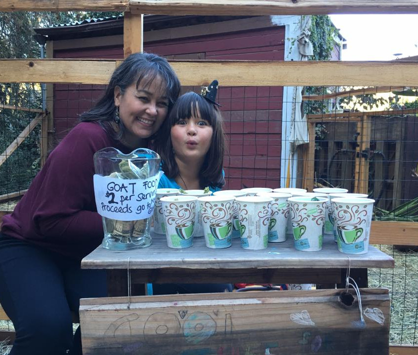 A mother and daughter in front of a table of cups