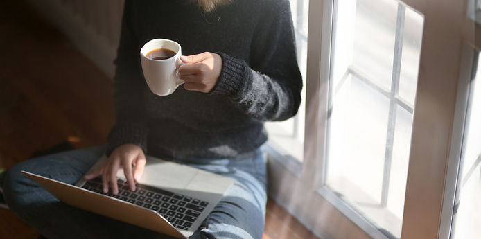 woman-using-laptop-while-holding-a-cup-o