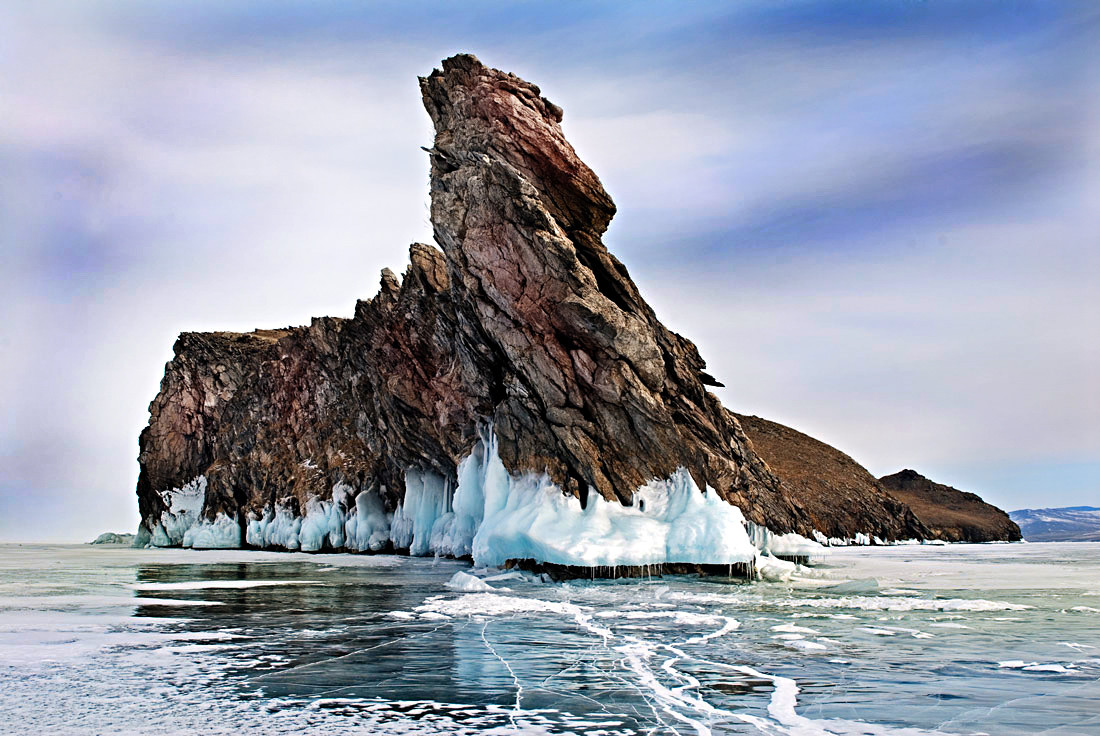 big frozen lake baikal with a rock in the middle