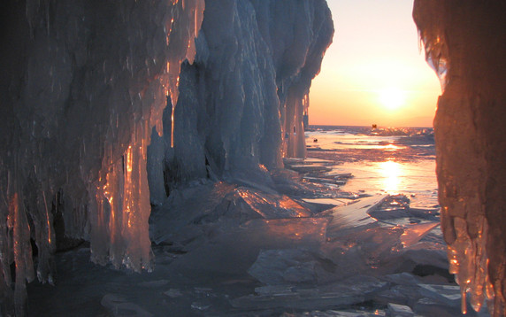 big cave in a  frozen lake baikal at sunset