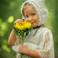 girl in the woods with a sunflower