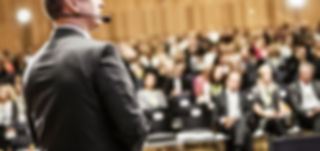 Foto Coaching Lerneffekt Mann Vortrag vor großem Publikum