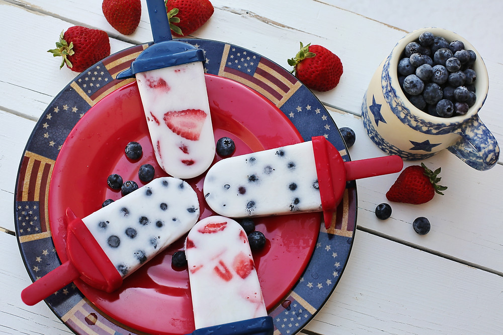 Patriotic popsicles with blueberries, strawberries on a plate