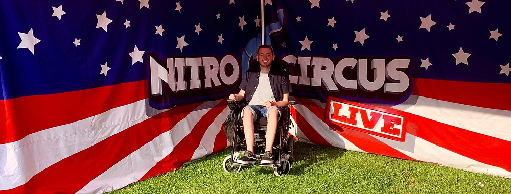 Ross parked in his wheelchair beside a large Nitro Circus sign