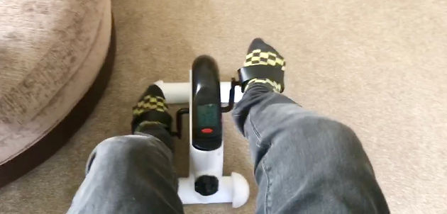 Ross using his feet to pedal exercise bike