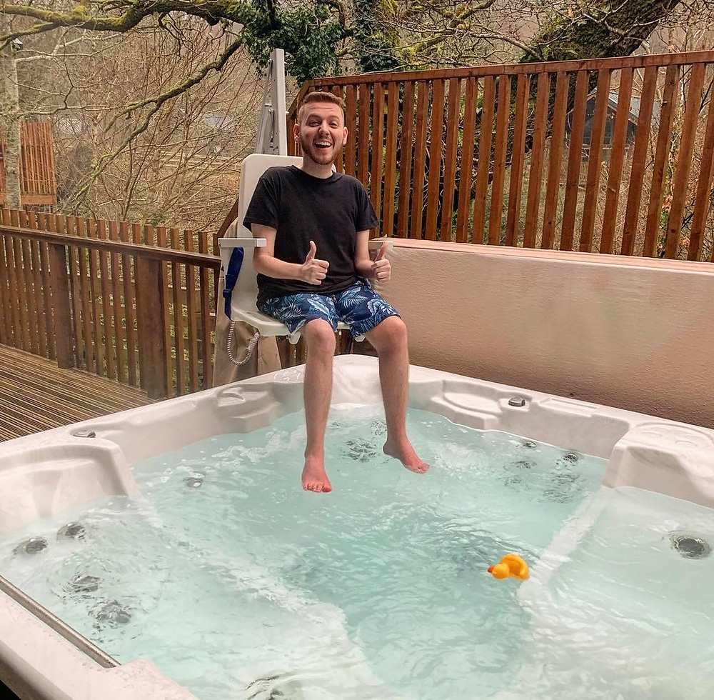 Ross sat in the hoist, hovering about the hot tub