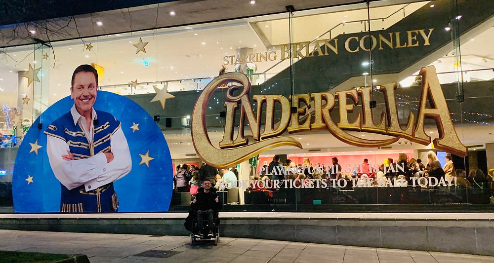 Ross outside the theatre, sat in his wheelchair beside a large Cinderella poster printed on the wall