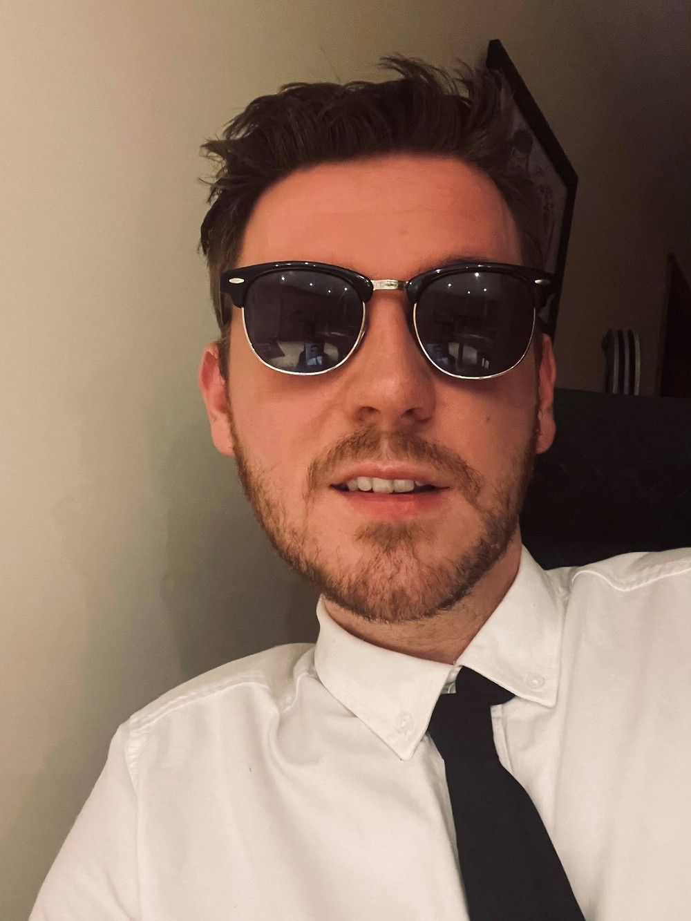 Selfie of Ross wearing a white shirt and black tie, with black sunglasses