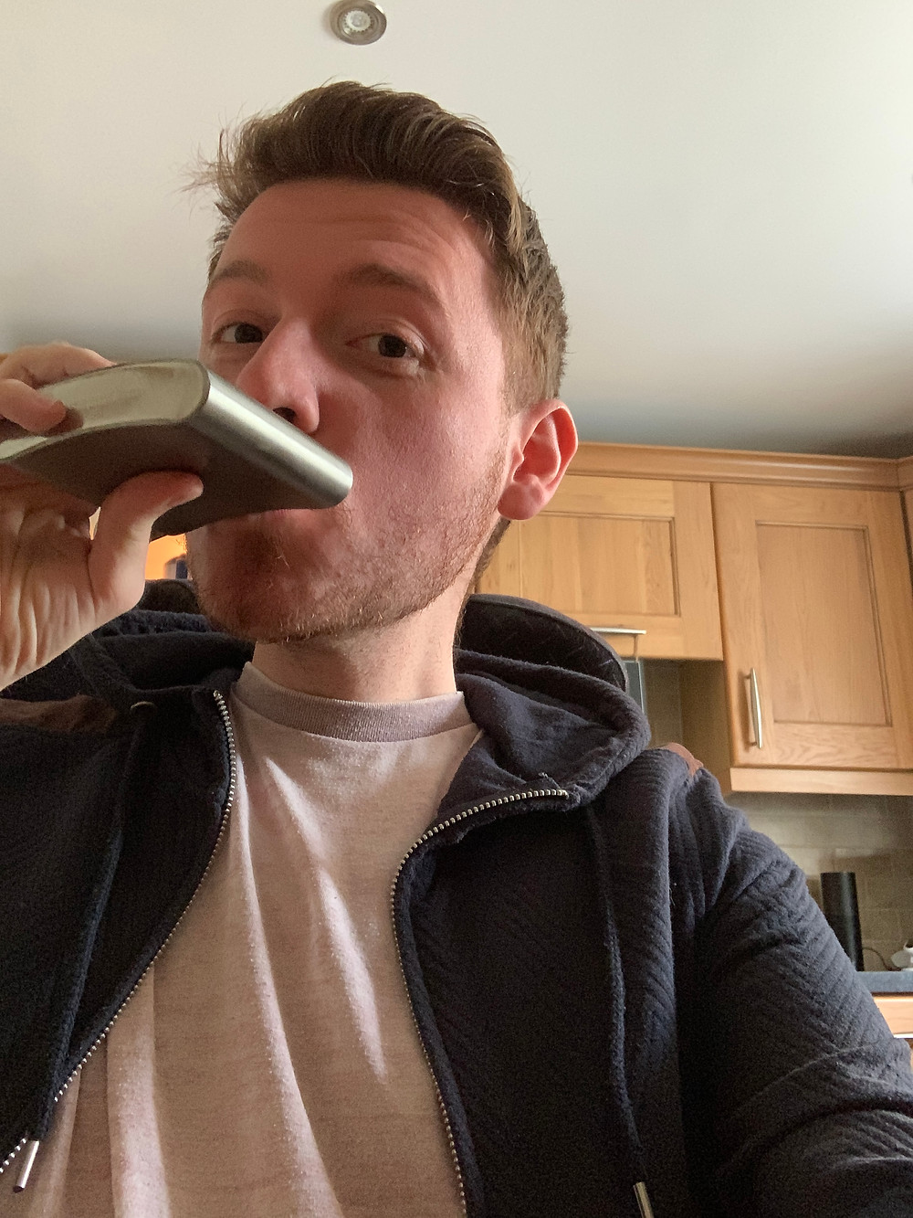 Selfie of Ross swigging a drink from a hip flask