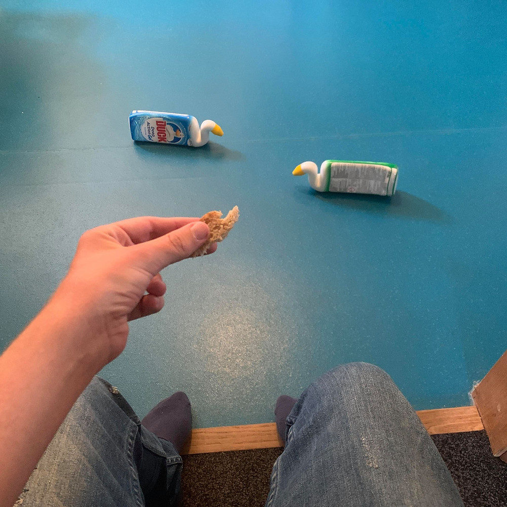 Ross's wrist holding a chunk of bread, with toilet ducks on the floor