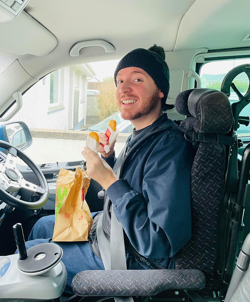 Ross sat in his car in the driving position, holding two hashbrowns and a mcdonalds bag