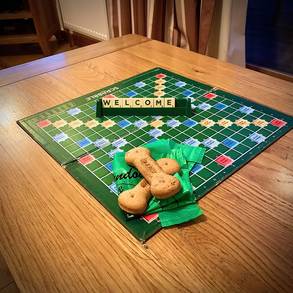 """Scrabble board spelling out the words """"WELCOME"""", alongside two dog biscuits from staff"""