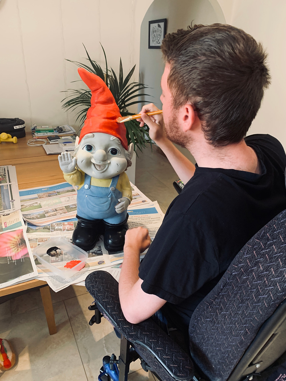 Shot of Ross from behind, painting one of his gnomes