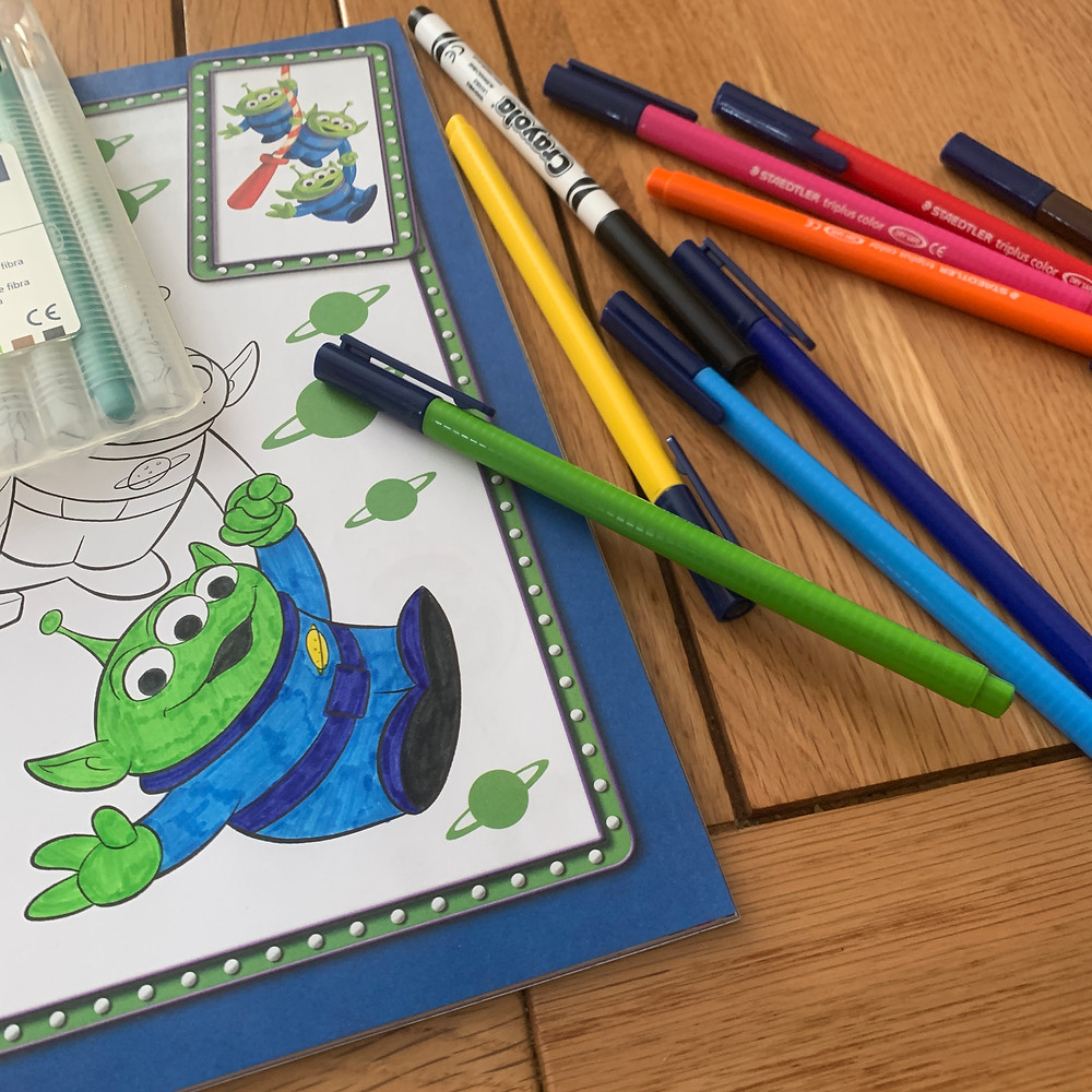 Colouring pens scattered across Ross's kitchen table, with a half coloured green toy story alien