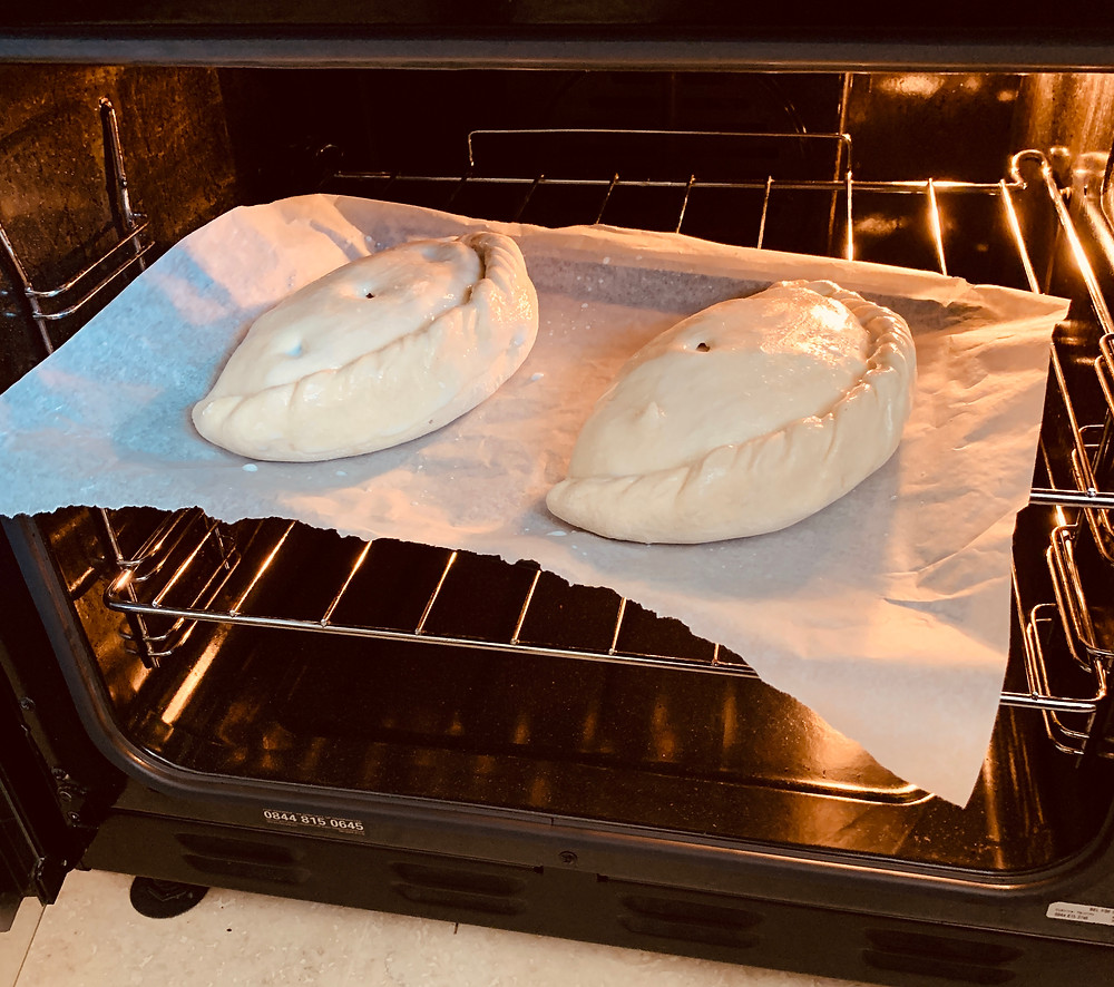 Two frozen pasties being placed inside Ross's oven