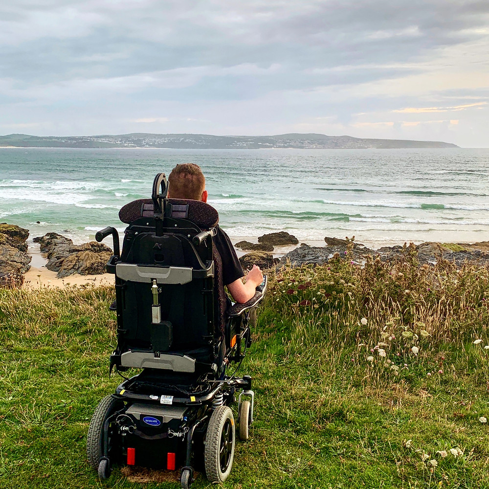 A shot of Ross's wheelchair from behind, as he overlooks the sea from the cliffs at Godrevy beach