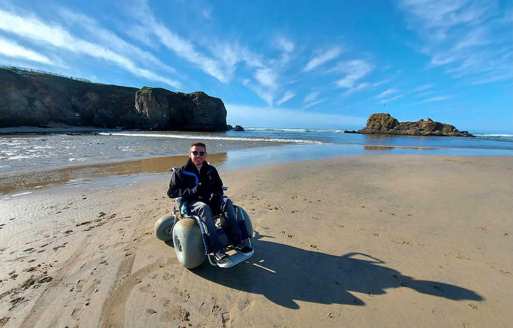Ross sat in the beach buggy chair, blue skies and sea in the background