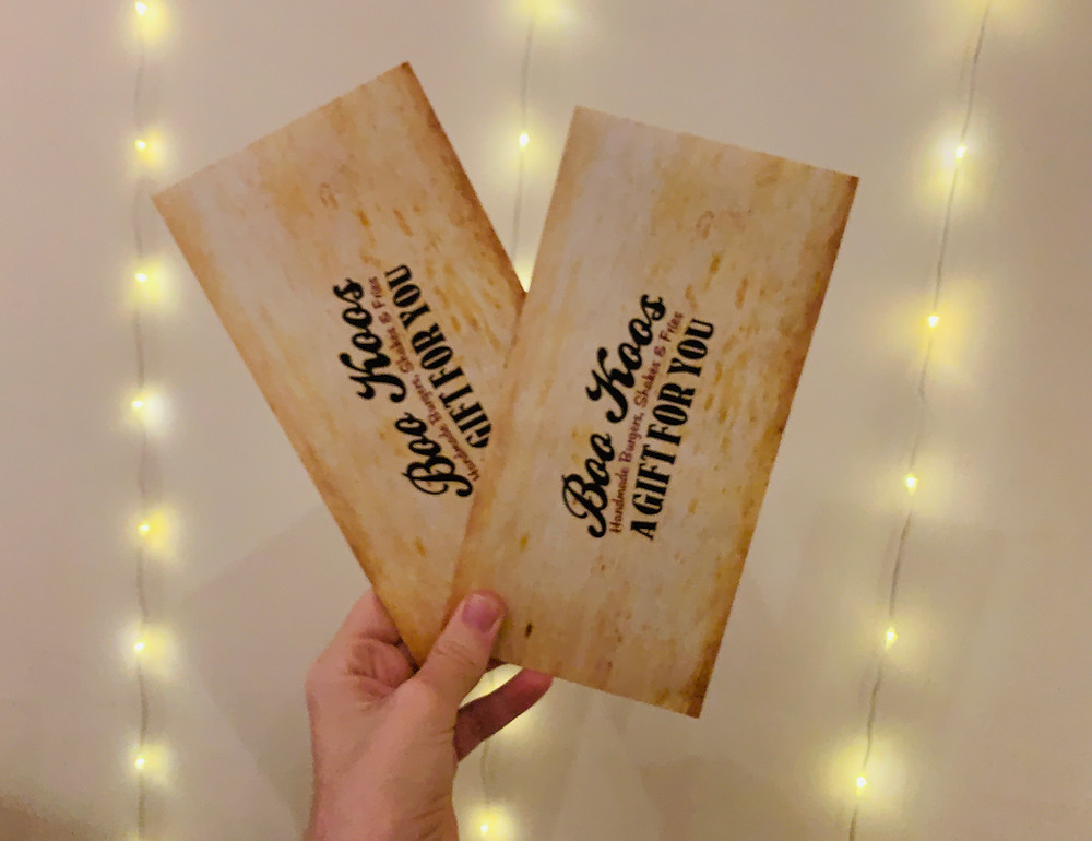 Two vouchers held up against a fairy light background