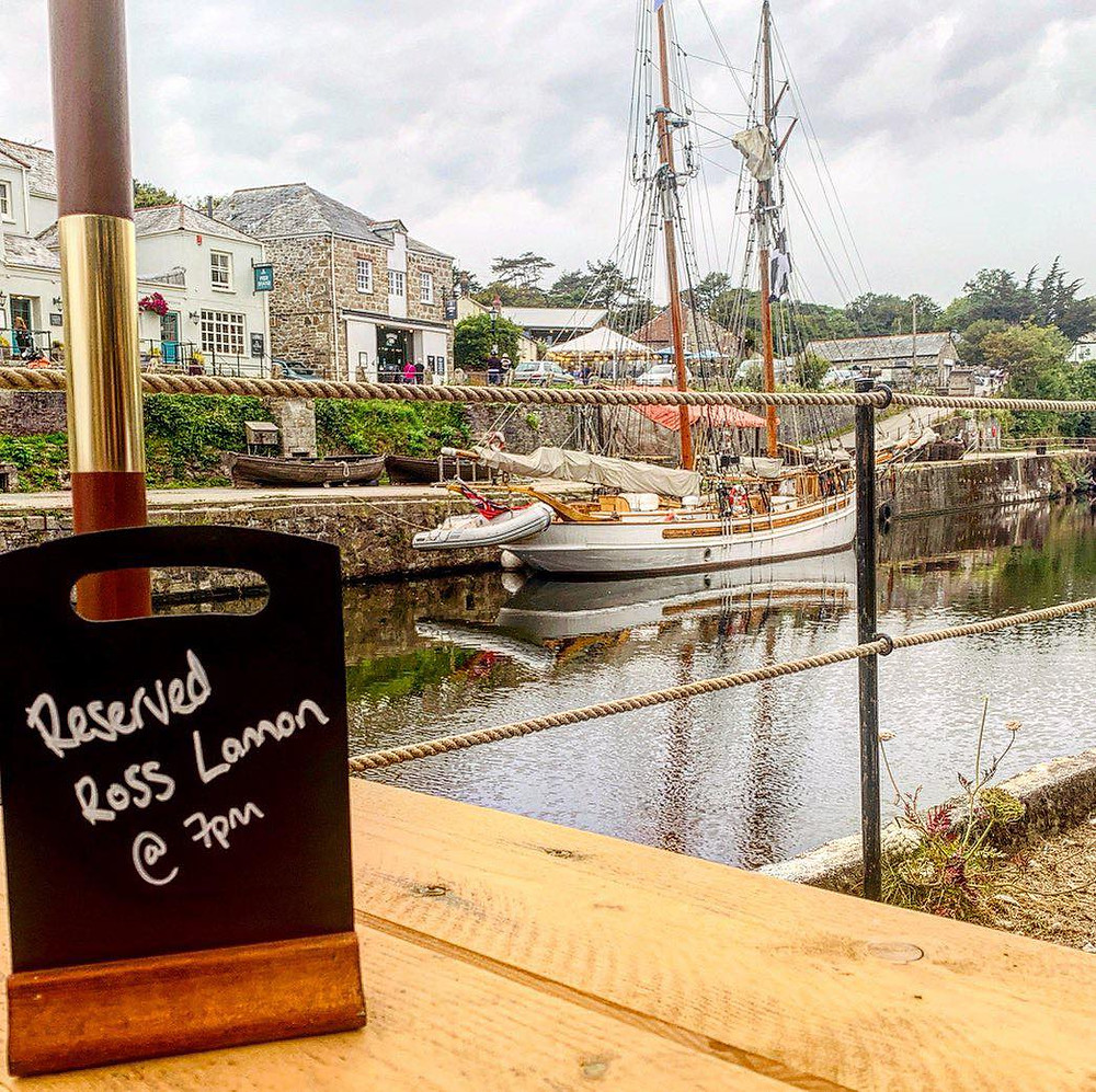 """Via from our table over the harbour, with a boat in the background. Sign on the table """"Reserved for Ross Lannon @7pm"""""""