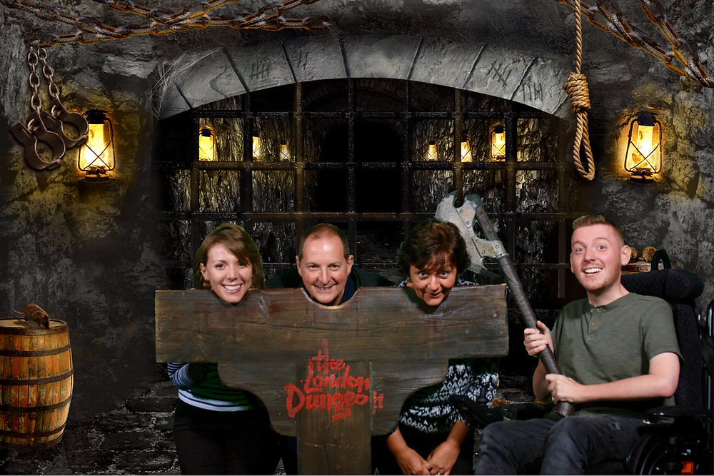 The Lannon family with their heads in the stocks, Ross holding the axe