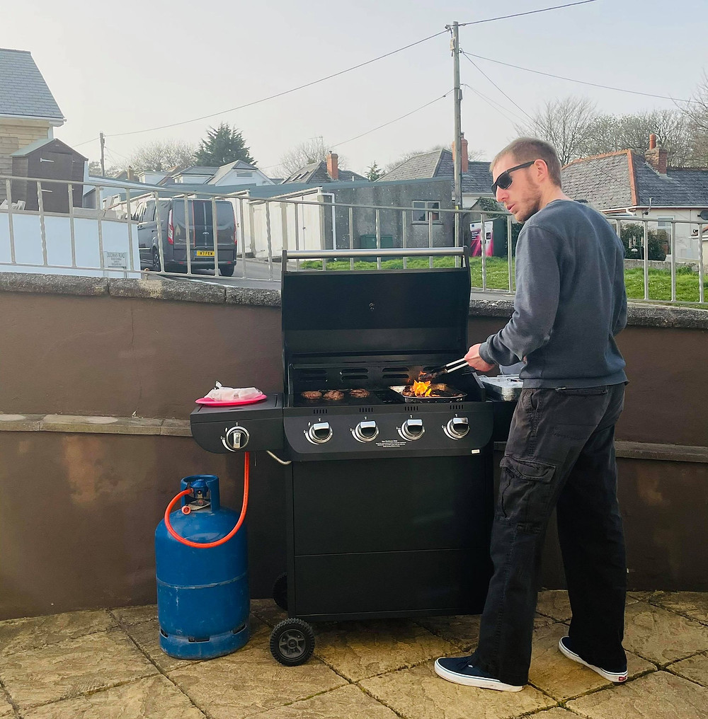 Ross's friend stood at the BBQ with flames coming off the grill