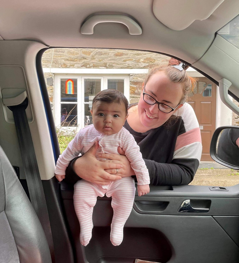 Ross's friend holding a baby sat on his car window sill