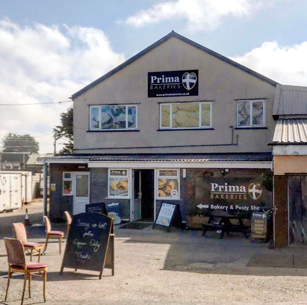 Photo of the outside of Prima Bakeries store, showing the chairs and two metre distancing