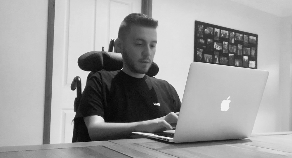 A black and white shot of Ross typing on his laptop, sat at his kitchen table in is wheelchair