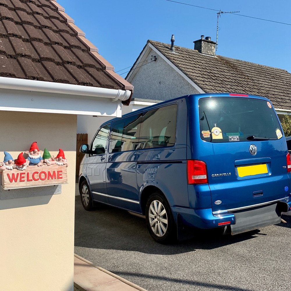 Ross's van parked outside his house, gleaming in the sun. Blue VW Caravelle Nevada