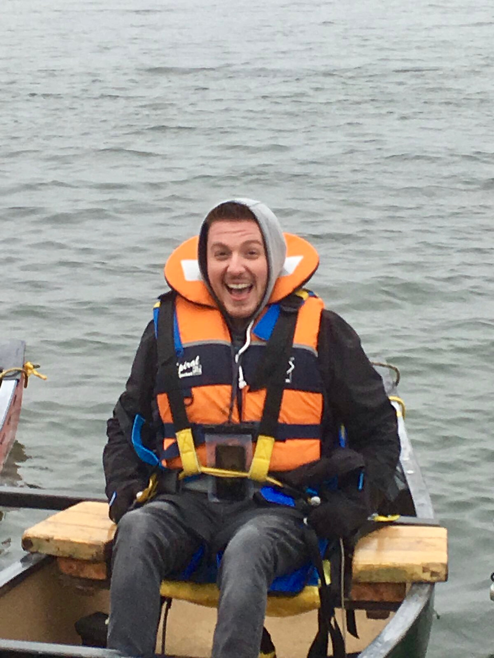 Ross wearing his life jacket, sat in the canoe