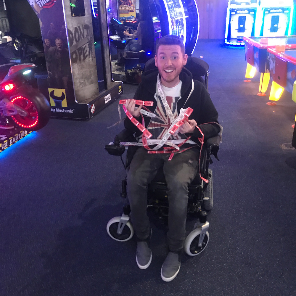 Ross in the arcades, holding all his winning ticket tokens