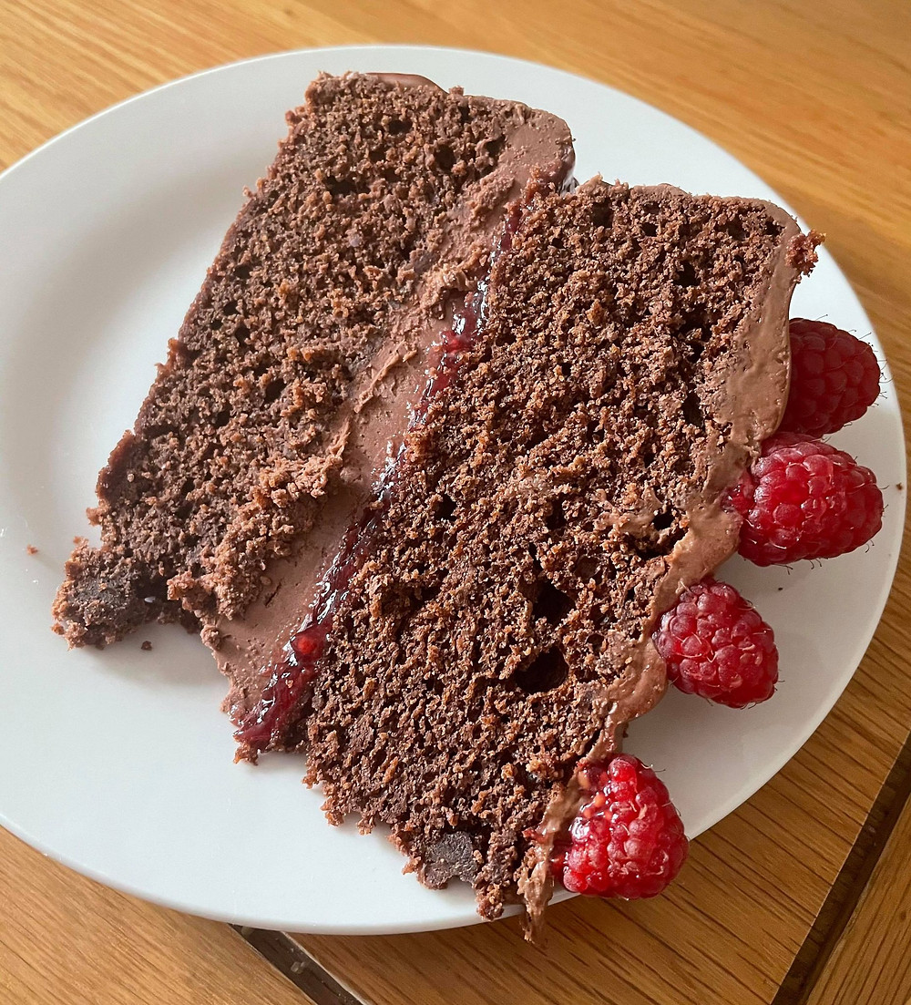 A portion of Ross's homemade chocolate and raspberry fudge cake cut on a plate