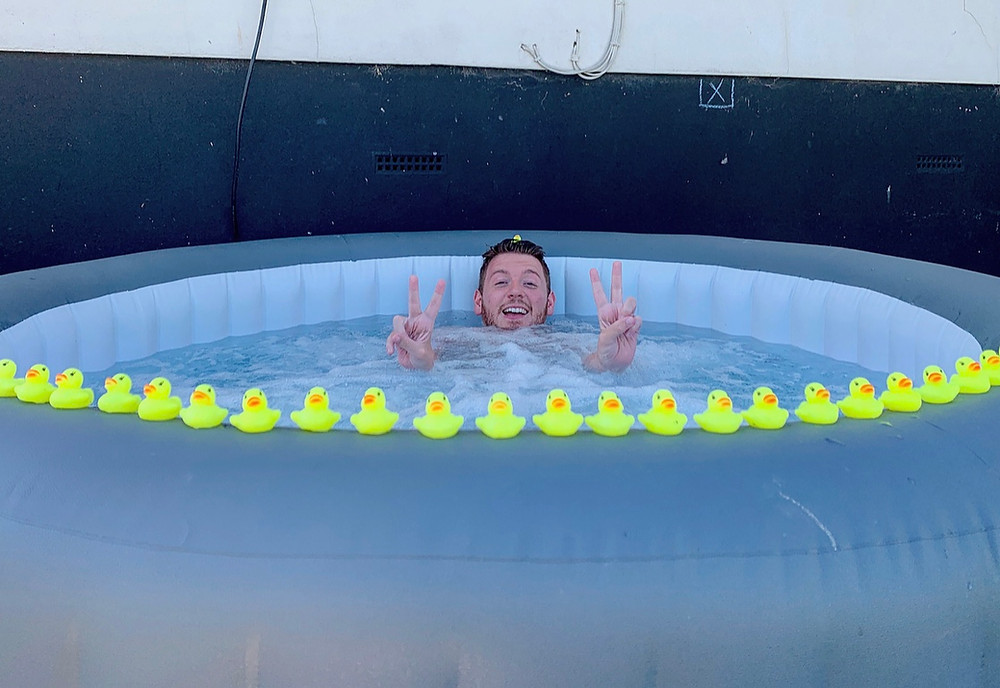 Ross relaxed in the hot tub, creating the peace sign with his hands. 40 rubber ducks positioned around the edge of the tub