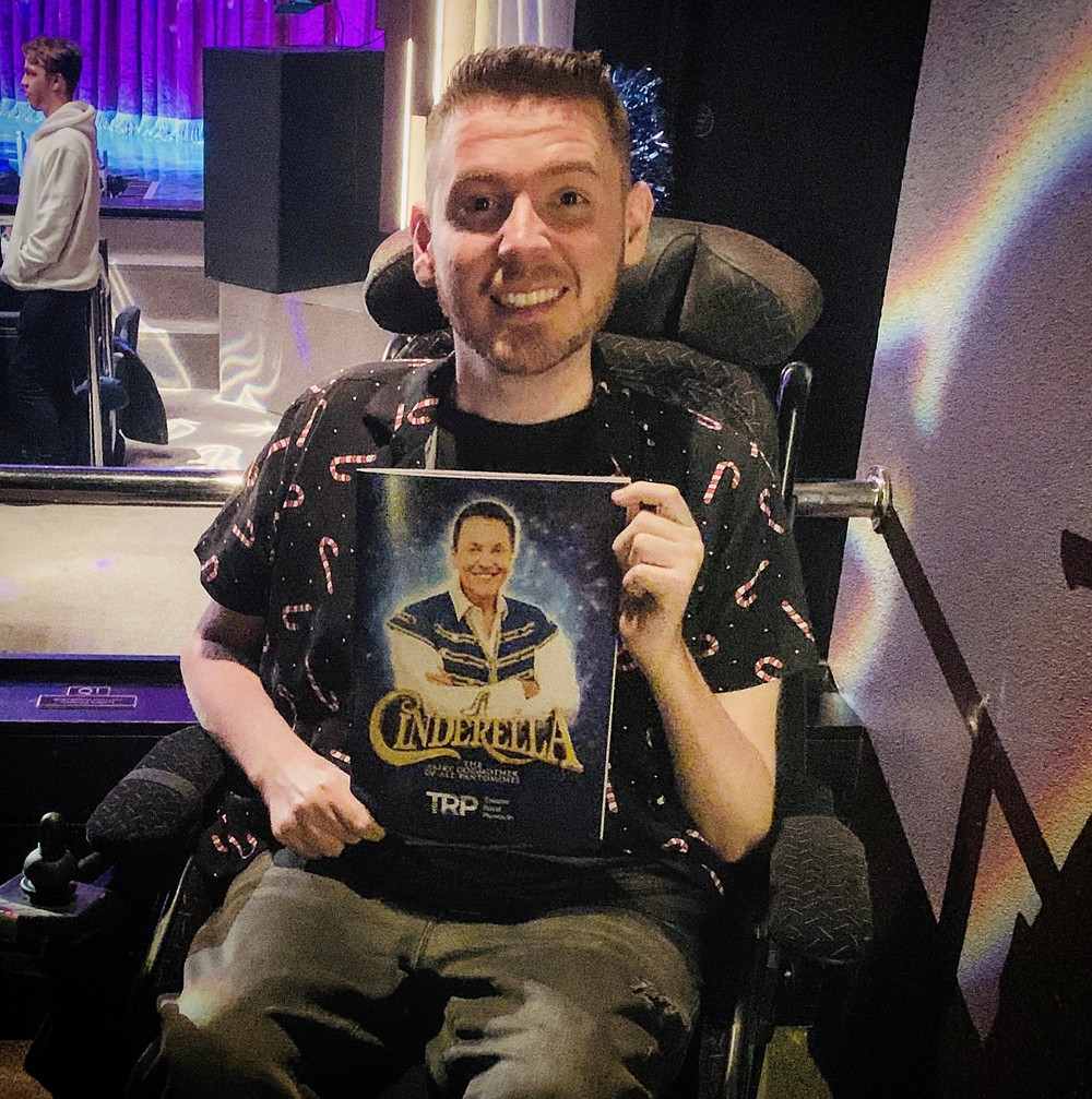 Ross inside the Theatre Royal, holding up his Cinderella programme