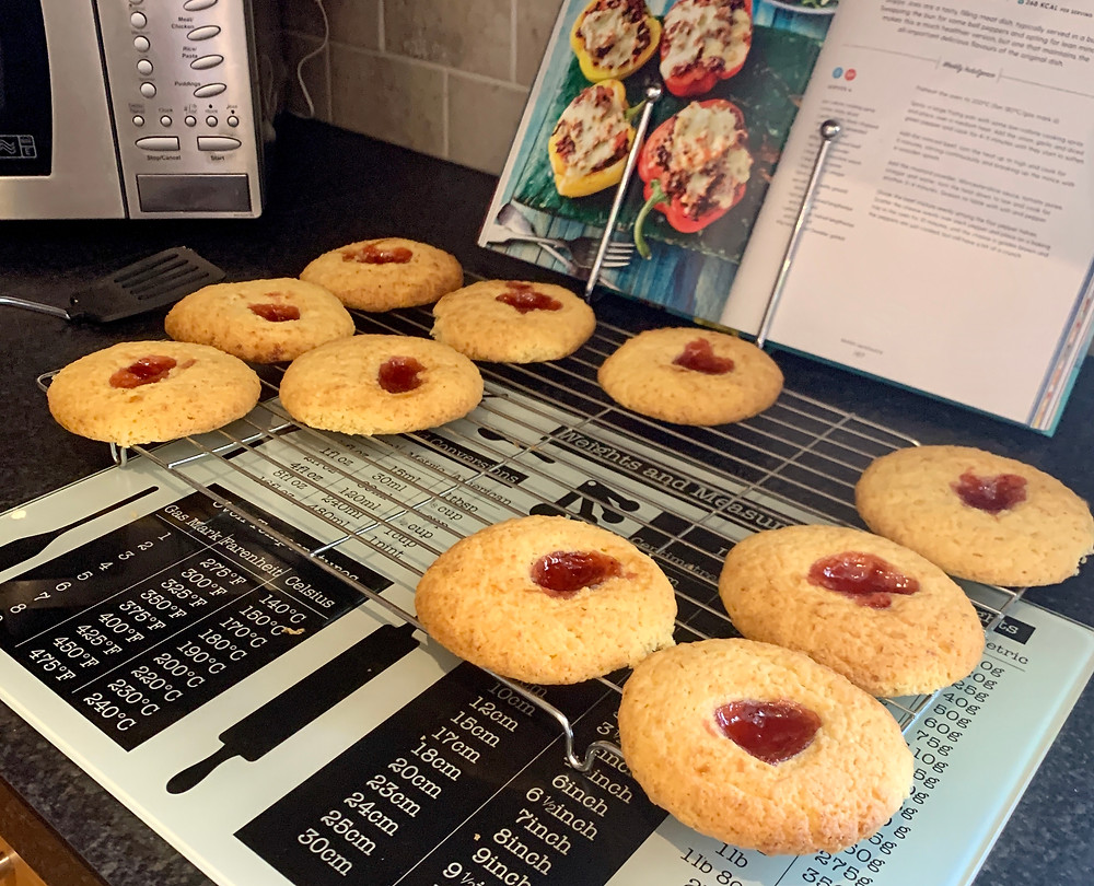 Jam & coconut biscuits spread out on a cooling tray in Ross's kitchen