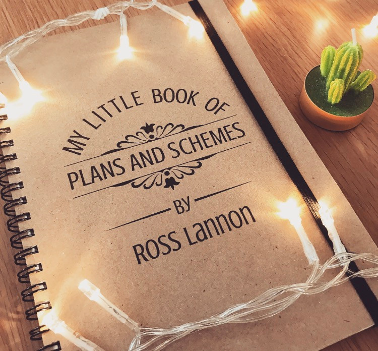 "Flat lay - a notebook with the title ""My little book of plans and schemes"""